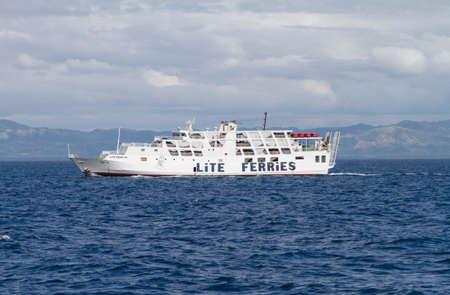 choppy: Side view of small white ferry in choppy seas beneath cloudy sky off Bohol Island, Philippines
