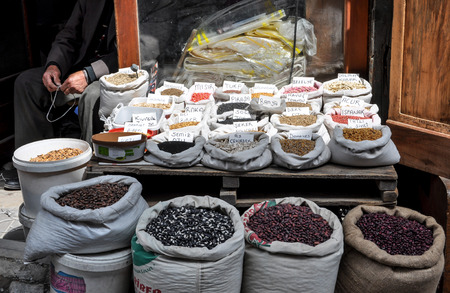 heaped: Spice market stall with heaped sacks and vendor in background Stock Photo