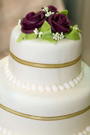 Wedding cake with white icing decorated with marzipan roses Stock Photo