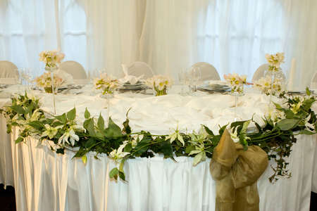 Table set for a wedding dinner decorated with flowers and a silk bow