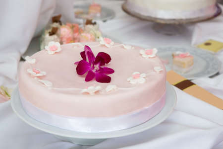 Wedding cake with pink icing decorated with an orchid flower photo