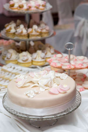 Wedding celebration with pink cake and icing decorated with rose petals photo