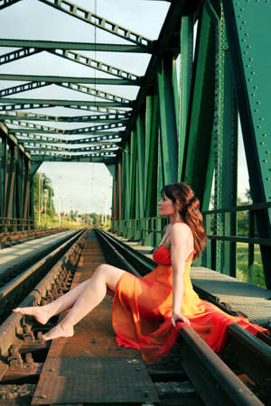 Young woman sitts on rail photo