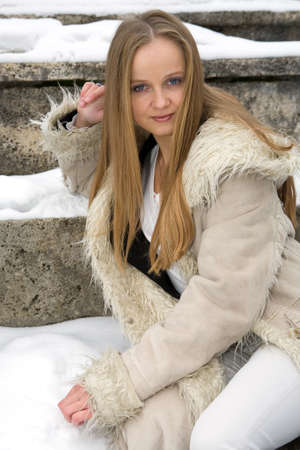 Blond freckled girl in fur coat on the snow photo