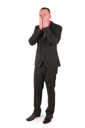 Young businessman covering face with his hands, isolated on white photo