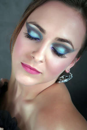 Beautiful woman wearing artistic makeup with her eyes closed photo