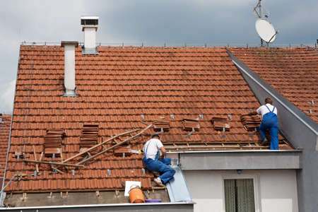 Zwei Männer arbeiten auf dem Dach Standard-Bild - 9784170