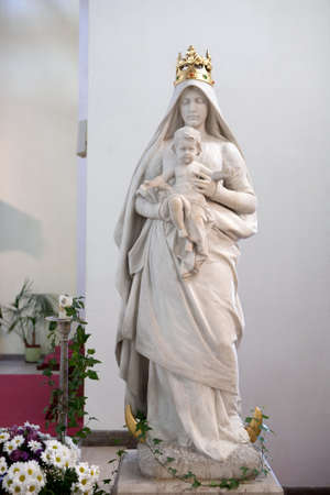 jesus standing: Statue of virgin Mary with baby Jesus standing on the moon Stock Photo