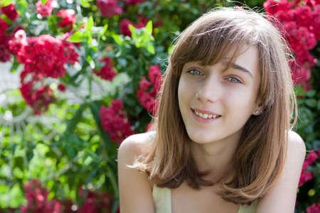 jeune fille adolescente: Portrait d'une adolescente dans le jardin de fleurs, copie espace sur la gauche