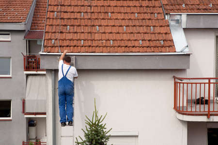Man on a ladder climbing on the roof Stock Photo