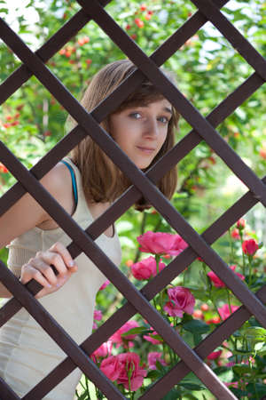 Teenage girl behind a fence photo