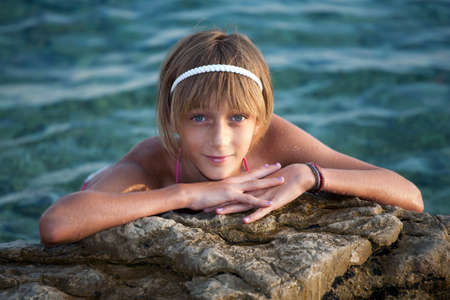 barrettes: Teenage girl relaxing on a rock near the sea Stock Photo