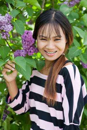 Beautiful Thai woman with braces in the park, shallow dof photo