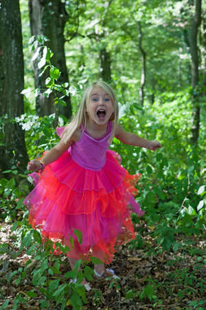 Little girl in princess costume - scream of joy in the forest Stock Photo