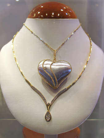 Golden necklace with a heart pendant on a mannequin photo