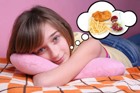 lying in bed: Teenage girl resting on the bed and dreaming of food Stock Photo