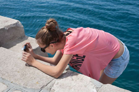 hot pants: Teenage girl taking photos by the sea