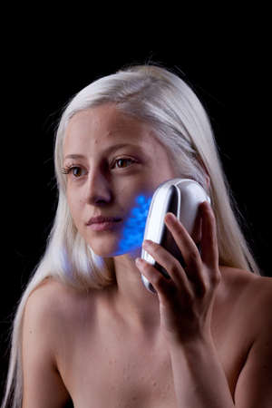 impure: Young woman with skin problems getting phototherapy by blue light