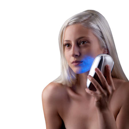 Young woman getting face phototherapy treatment by blue light Stock Photo - 14443069