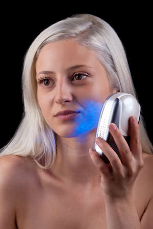 Young woman getting photo-therapy treatment with blue light Stock Photo - 14545134