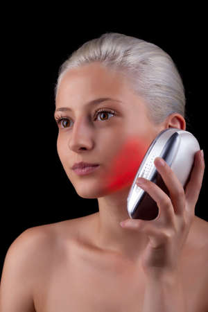 Young woman getting photo-therapy treatment with red light Stock Photo - 14545131