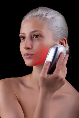 Young woman getting photo-therapy treatment with red light photo