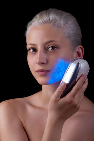 Young woman getting photo-therapy treatment with blue light  Stock Photo