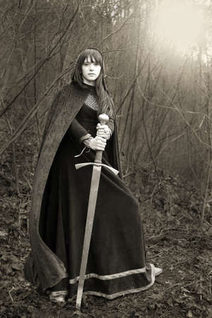 female warrior: Portrait of a medieval lady with sword  sepia toned  Stock Photo
