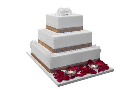 tiered: Elegant wedding cake decorated with rose petals and candles, isolated on white