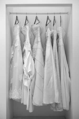 hanging woman: Collection of wedding dresses in the shop in black and white