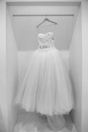 satin dress: Wedding dress on a hanger in black and white Stock Photo