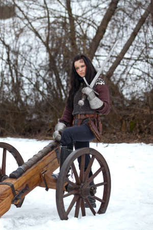 retribution: Woman in the medieval costume with a sword sitting on a cannon