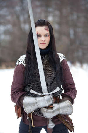 Beautiful young woman in medieval clothes holding a sword photo