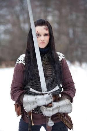 espadas medievales: Joven y bella mujer en ropa medieval con una espada