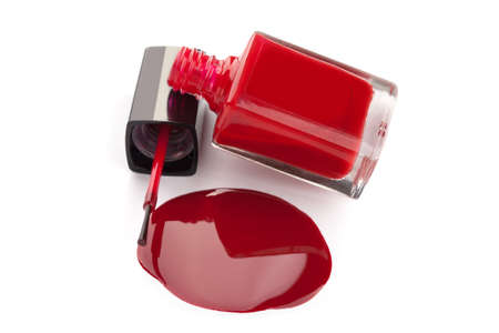 Red nail polish bottle with spilled varnish isolated on white background  photo