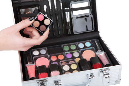 paint box: Opened aluminum make up case and female hand holding an eyeshadow palette