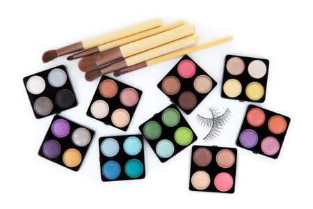 Various eyeshadow palettes, fake eyelashes and cosmetic brushes, isolated on white photo