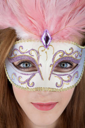 Beautiful teenage girl wearing carnival mask with pink feathers photo