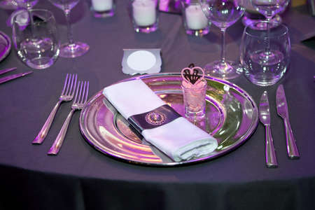 Detail of a wedding dinner setting with purple reflection on the tableware photo