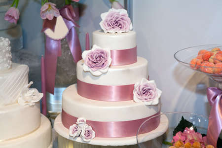 Wedding cake with roses at luxury reception photo