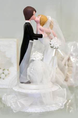 Bride and groom figurines kissing photo