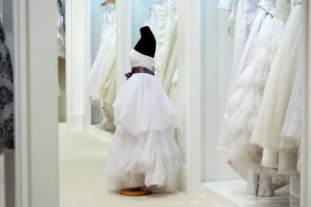 purple dress: The range of wedding dresses on hangers and on a mannequin in the showroom Stock Photo