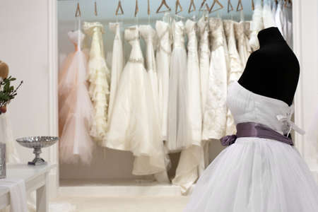The range of wedding dresses on hangers and on a mannequin in the showroom Stok Fotoğraf