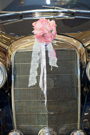 festooned: Vintage car with wedding bouquet Stock Photo