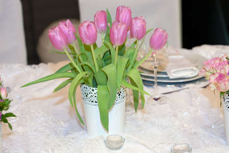 Table decorated with candles and tulips photo