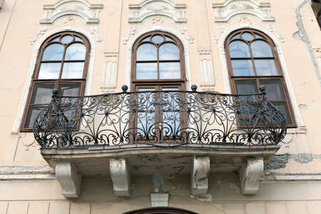 Balcony on a castle with three windows and the wrought iron banister