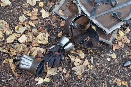 historical periods: Knight armor helmet and gloves on the ground covered with dry leaves Stock Photo