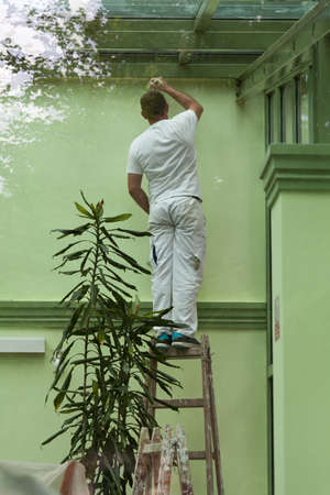 splotchy: A man standing on a ladder and painting walls in green, shot through a window