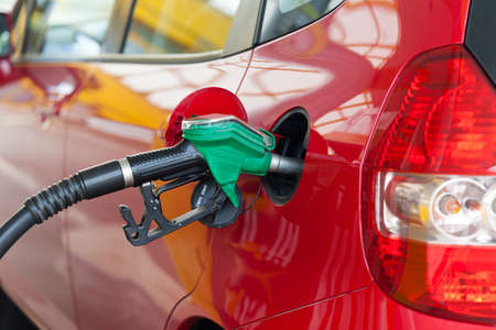 fuelling pump: Red car at gas station being filled with fuel Stock Photo