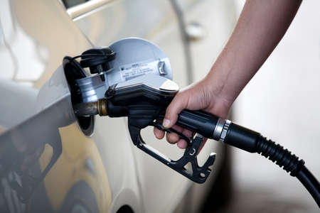 fuelling pump: Silver car at gas station being filled with fuel Stock Photo